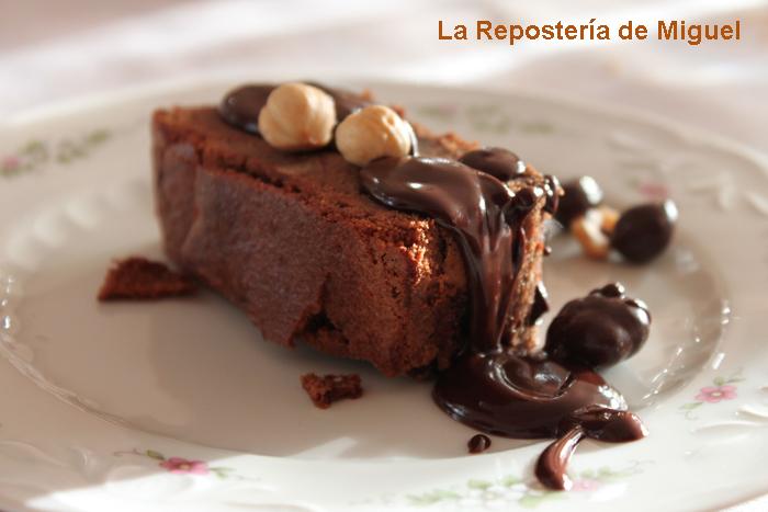 Porción de brownie de chocolate con nueces presentado en un plato con fondo blanco y ribetes verdes. La porción tiene una nuez encima y esta bañada de chocolate por encima.