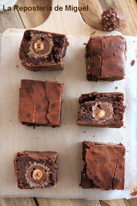 Seis porciones de del brownie sobre una tabla de madera para cortar, vistas desde arriba. Algunas de las porciones estan situadas para que se aprecie el bombón ferrero rocher que tienen en su interior.